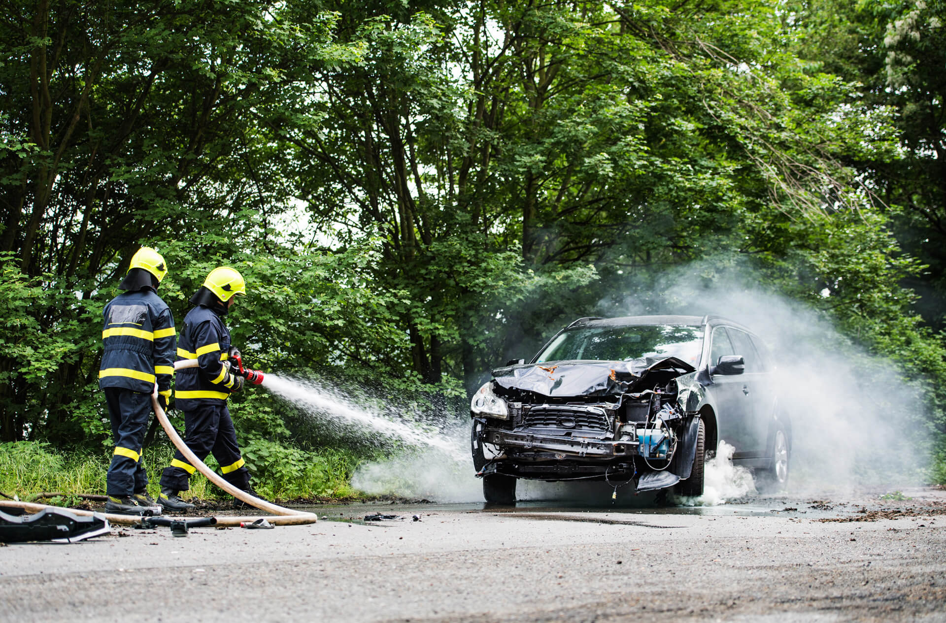 Two firefighters extinguishing a burning car after an accident