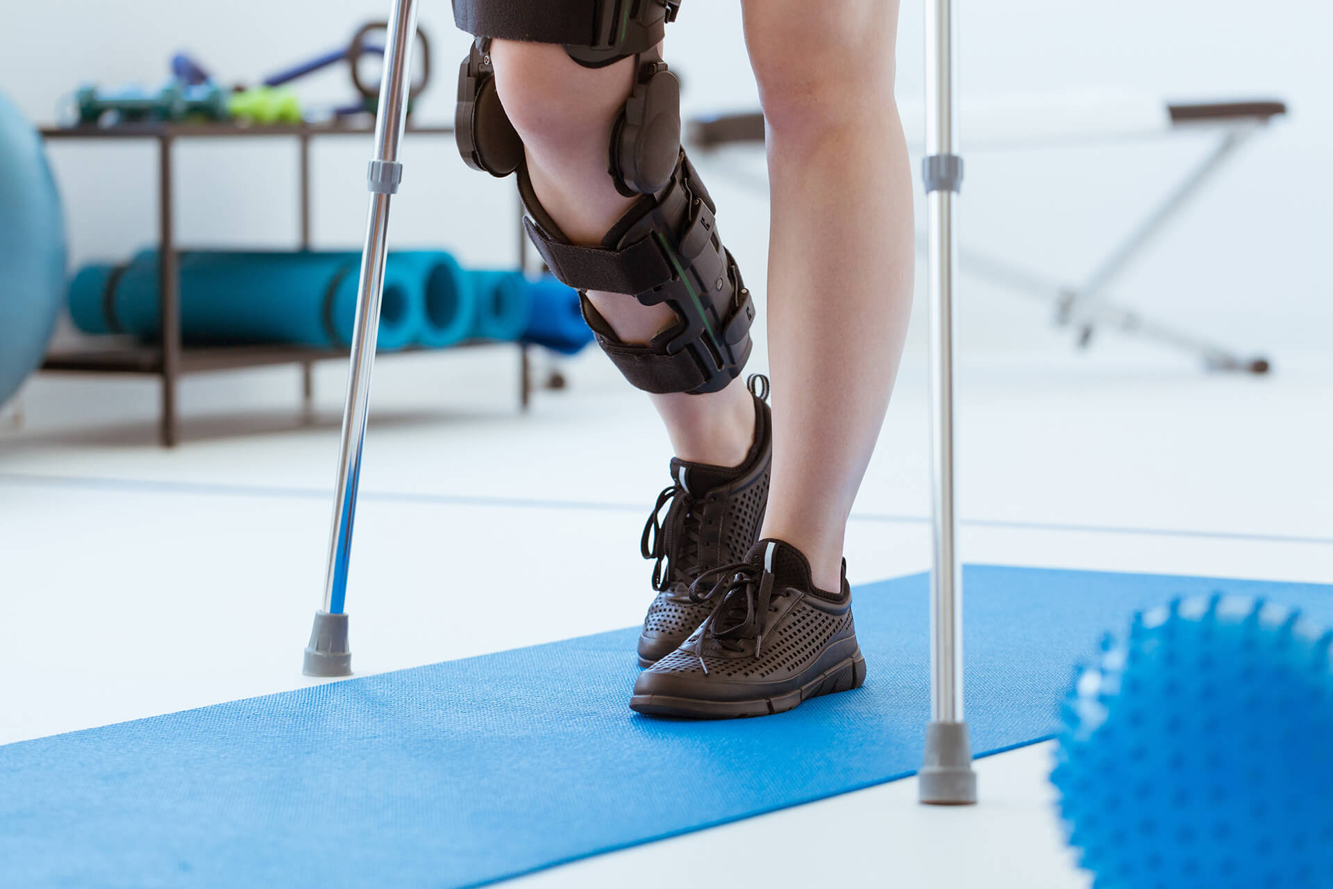 Injured patient in a leg brace exercising on a blue mat in a phy