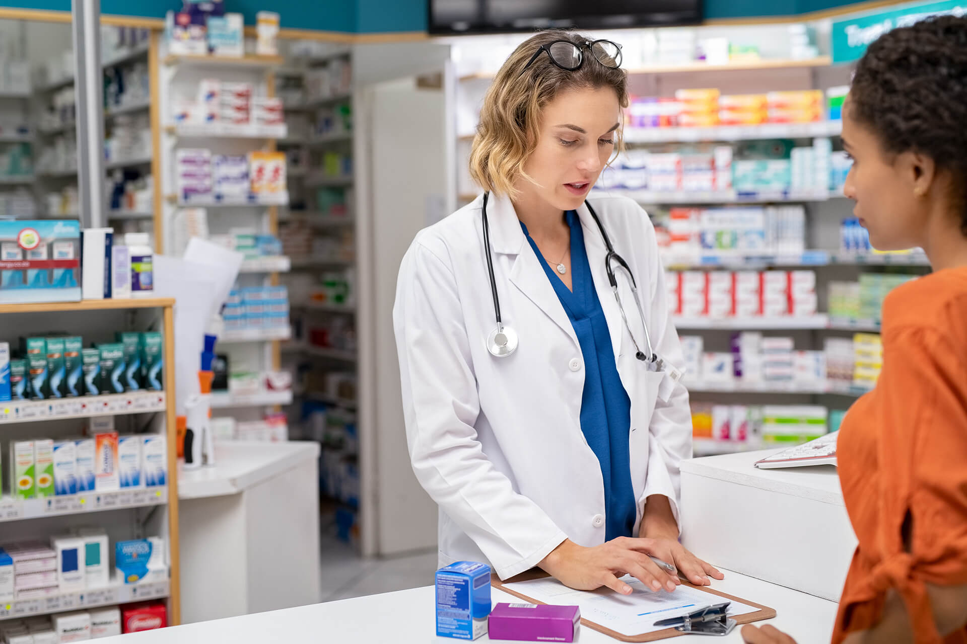 Woman pharmacist with prescription assisting a customer standing at the counter. Doctor  in drugstore suggesting medical drug to buyer. Druggist with prescription assisting and explaining dosage of medicines to young african woman with copy space.